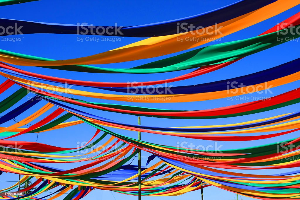 Multicolored ribbons hanging from poles under a blue sky royalty-free stock photo