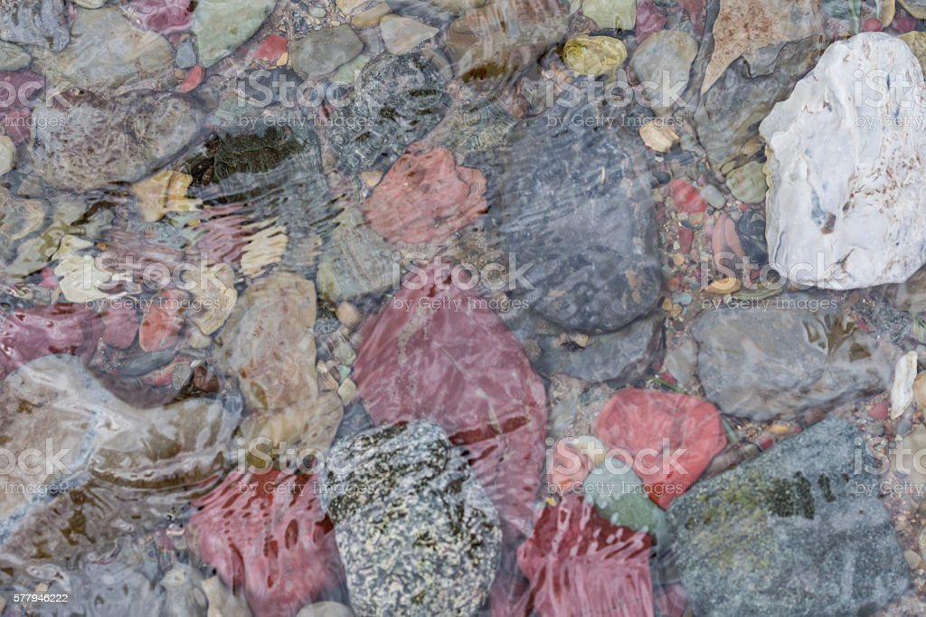 Multicolored Rocks below the ripples of Creek stock photo