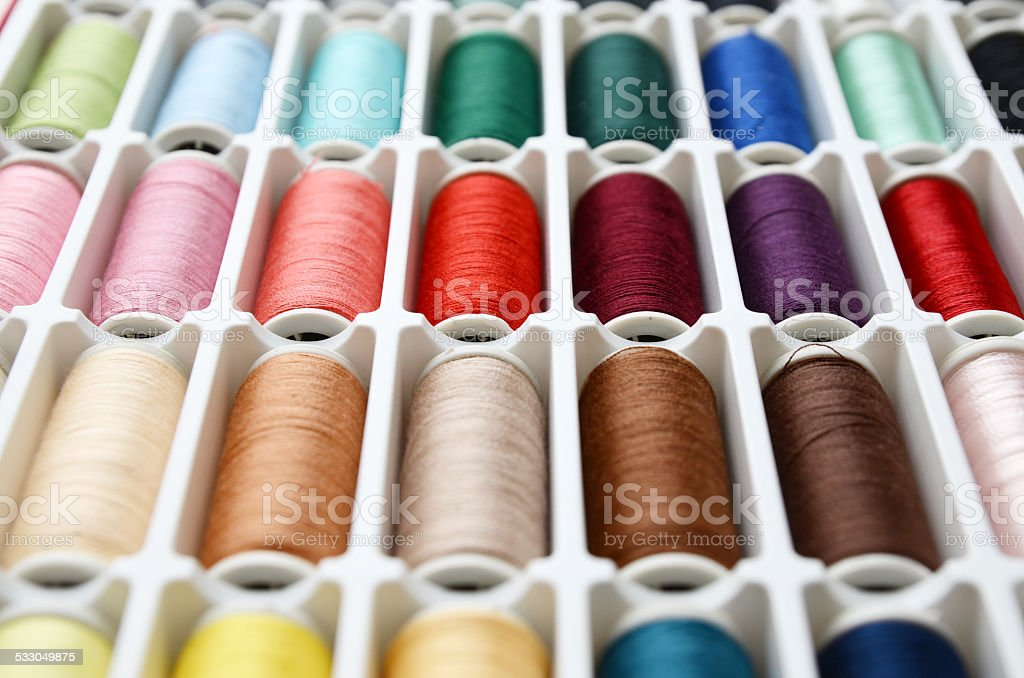 Multicolored sewing threads background closeup stock photo