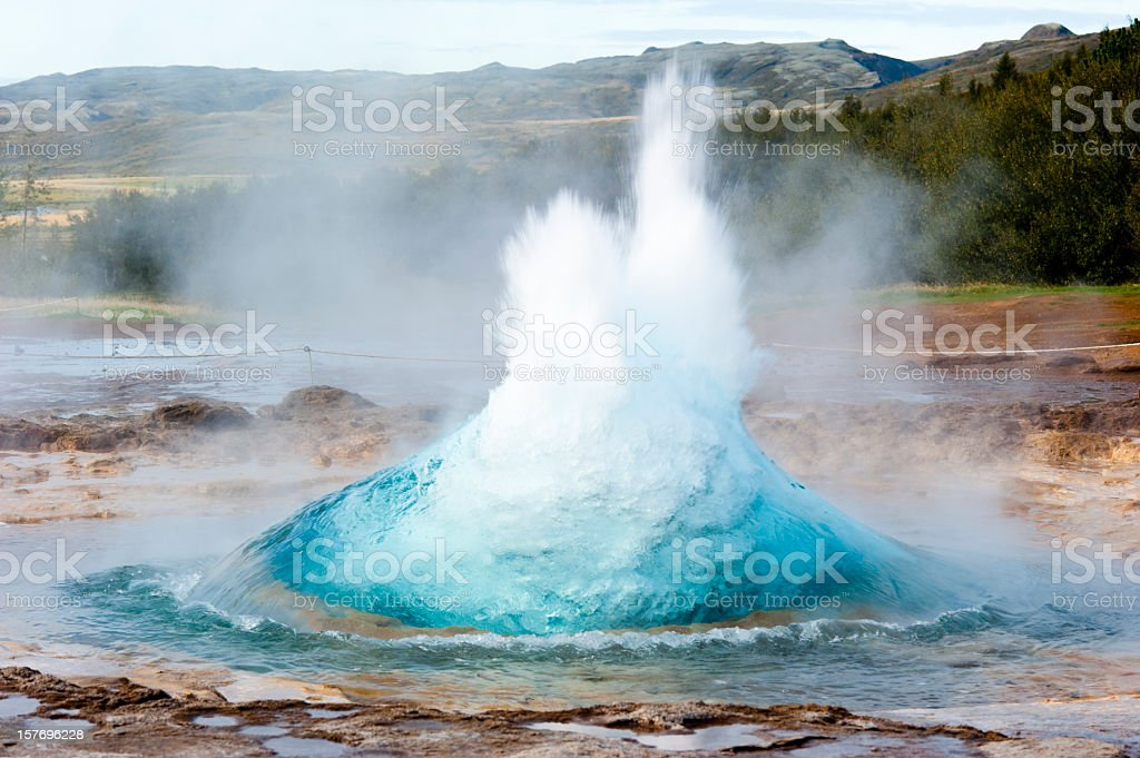 Multicolored strokkur with mountain range royalty-free stock photo