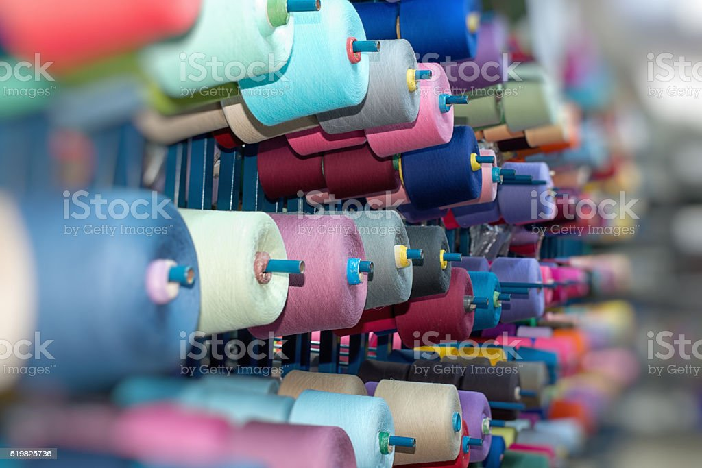 Multicolored thread spool in storehouse shelf stock photo