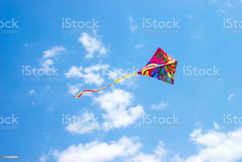 Multicolored tie dyed kite flying in the blue sky stock photo