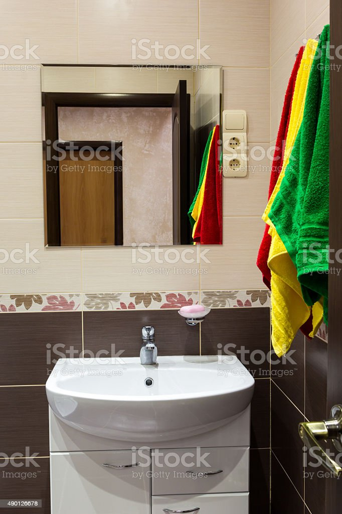 Multicolored towels over the sink in bathroom stock photo