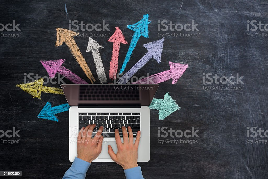 Multicoloured hand drawn arrows going out of the laptop stock photo