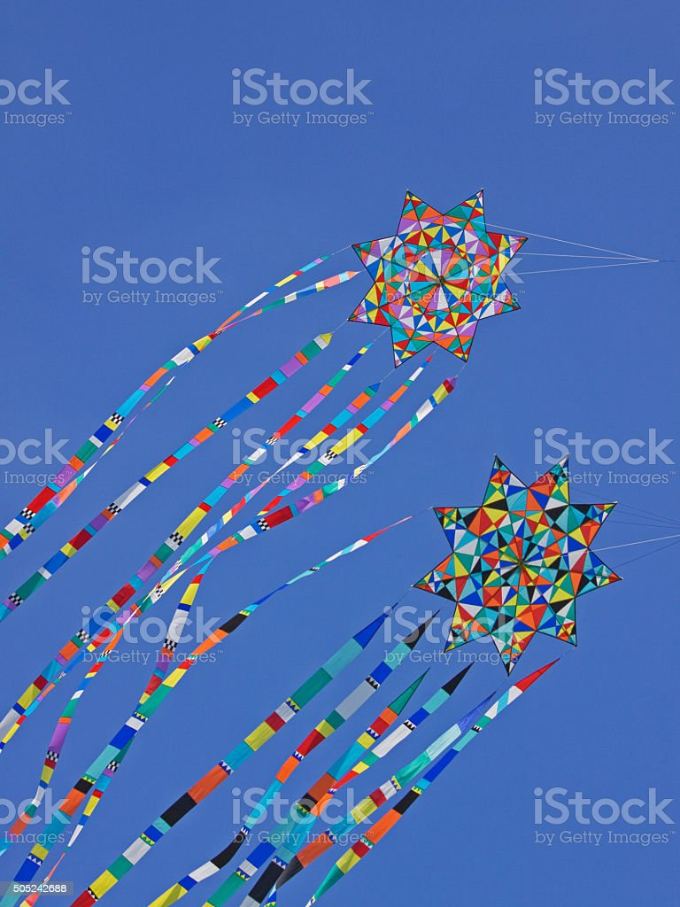 Multi-coloured kites in flight in a strong wind stock photo