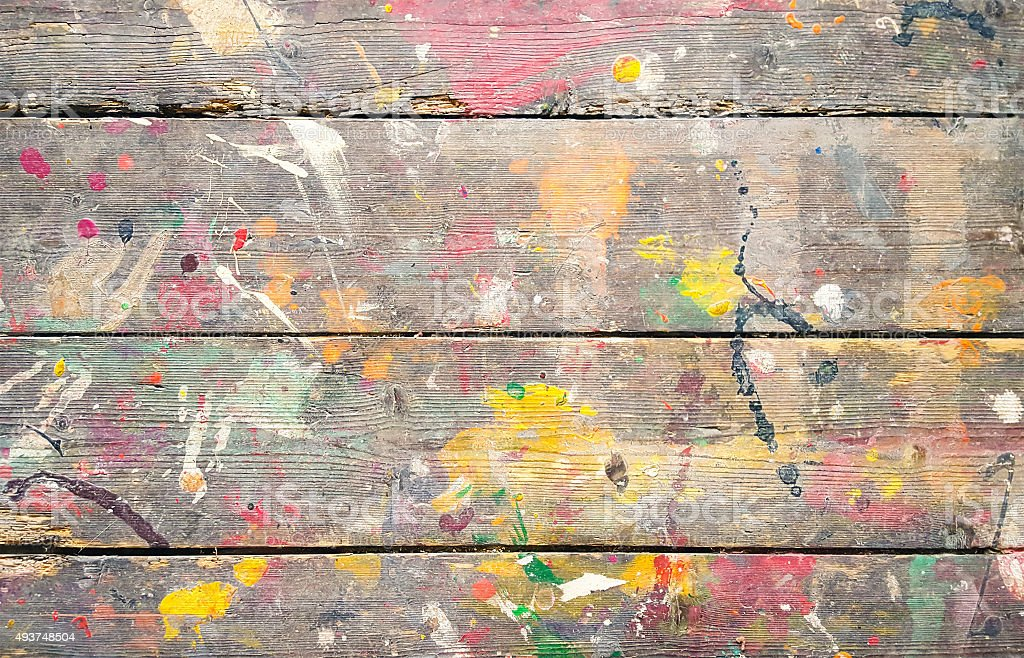 Multicoloured paint splatters on weathered wooden floorboards. stock photo