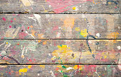 Multicoloured paint splatters on weathered wooden floorboards.
