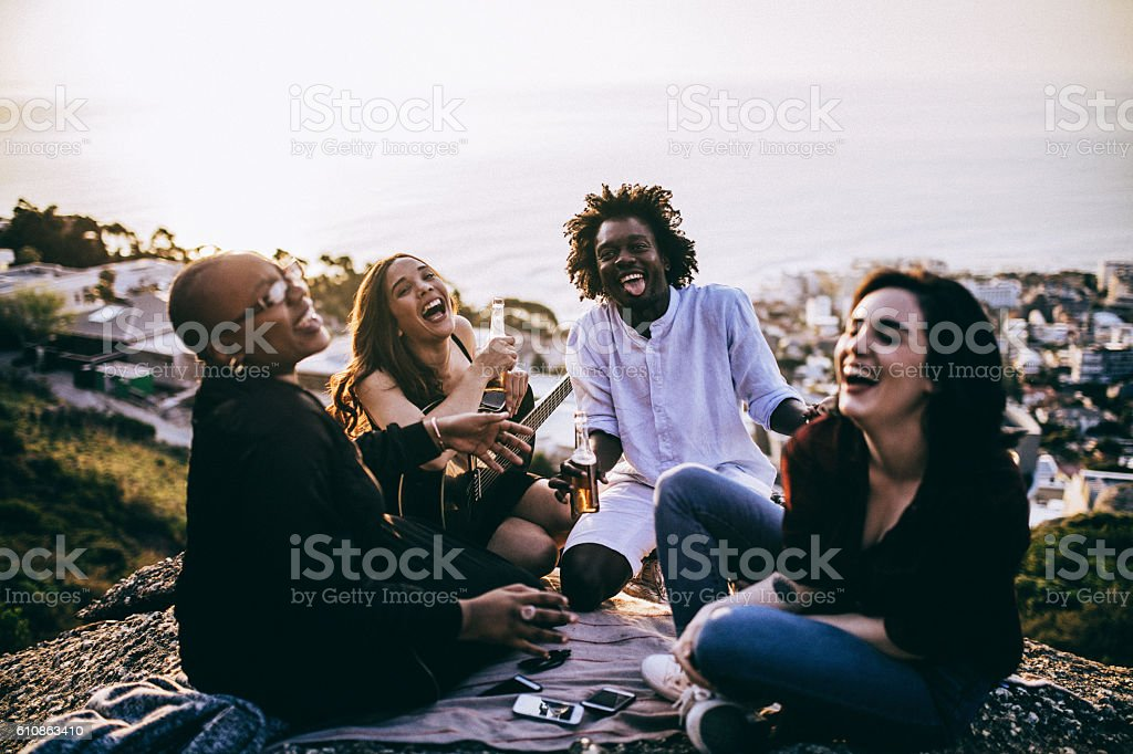 Multicultural group of young adult friends talking to each other stock photo