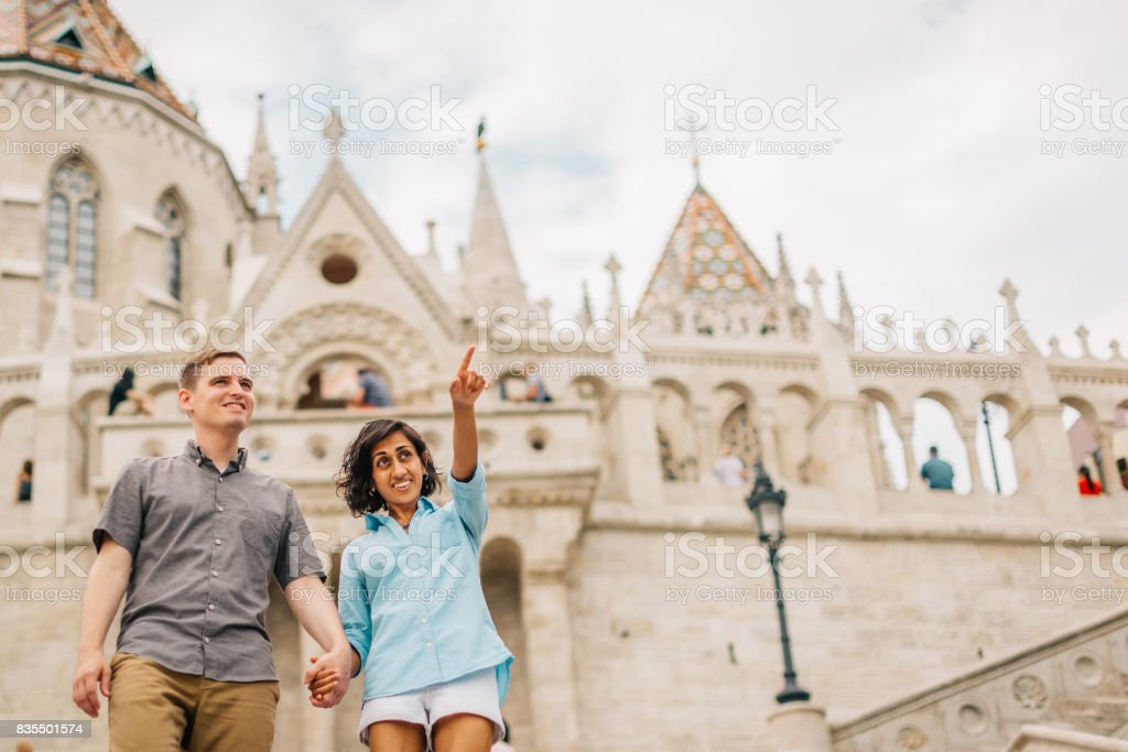 Multicultural Happy Couple Tourists Walking Down The Street Holding Hands   Honey Moon stock photo