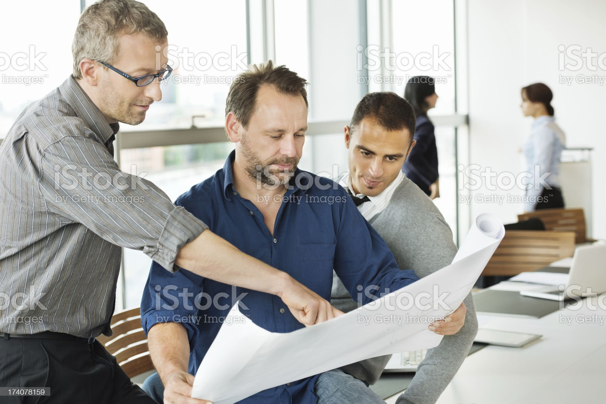 Multiethnic Architects Reviewing Blueprint royalty-free stock photo