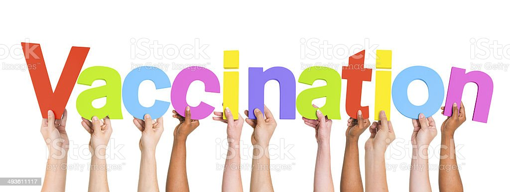 Multiethnic Arms Raised Holding Text Vaccination stock photo