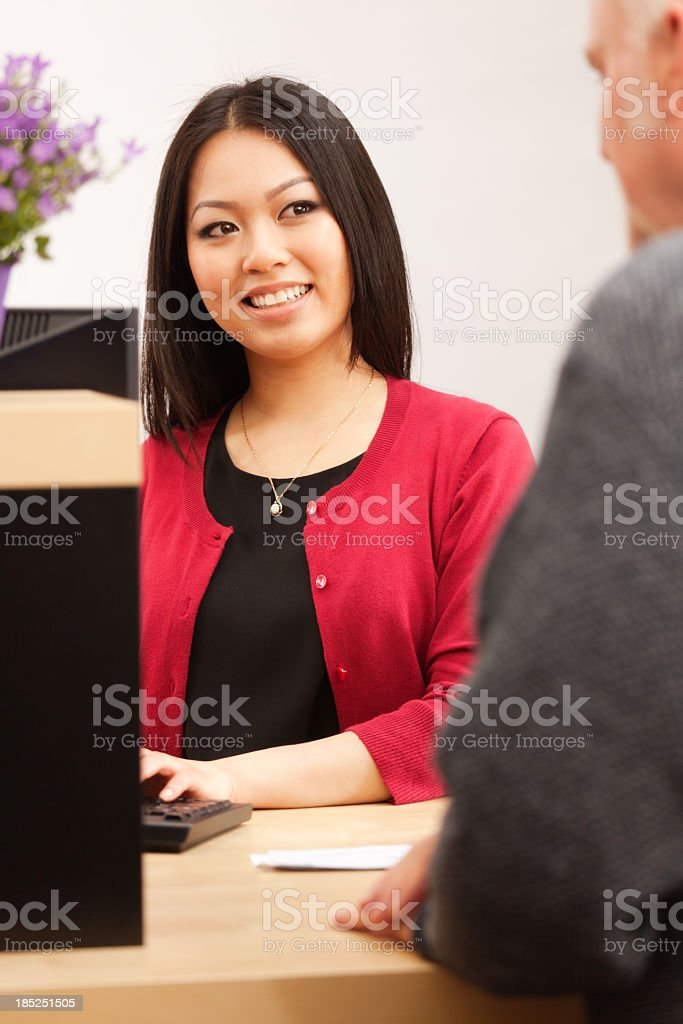 Multi-Ethnic Asian Bank Teller and Caucasian Customer at Bank Counter royalty-free stock photo