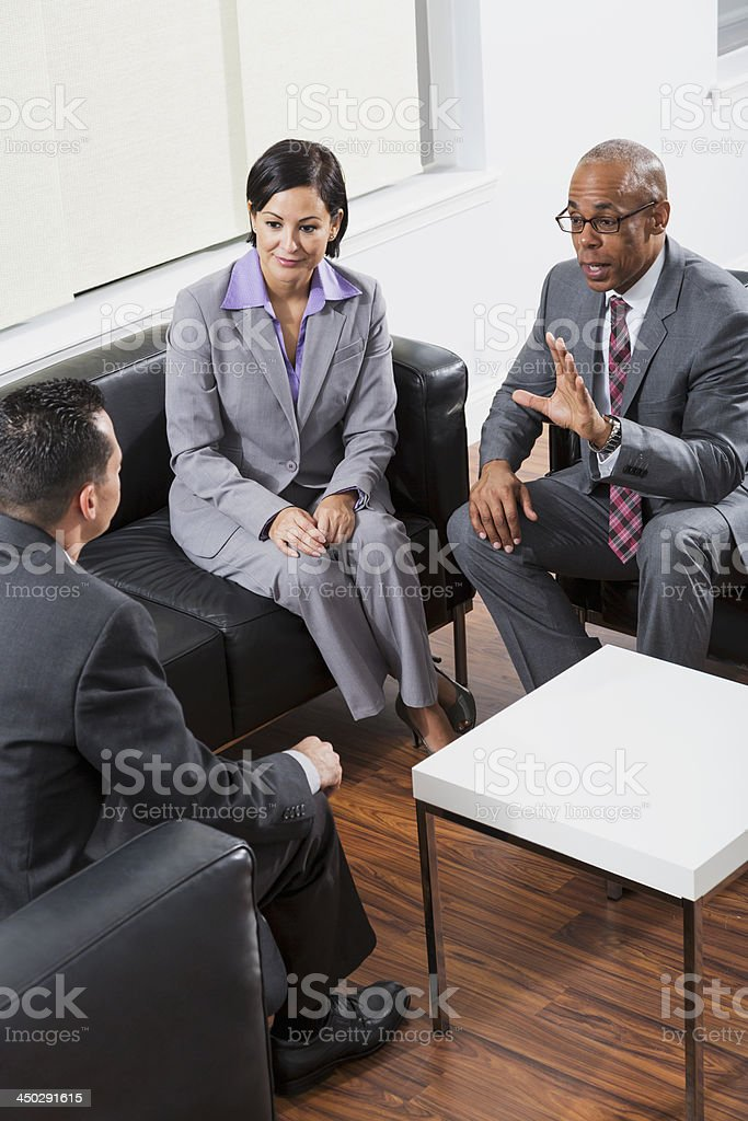Multi-ethnic buisnesspeople in suits in business meeting royalty-free stock photo