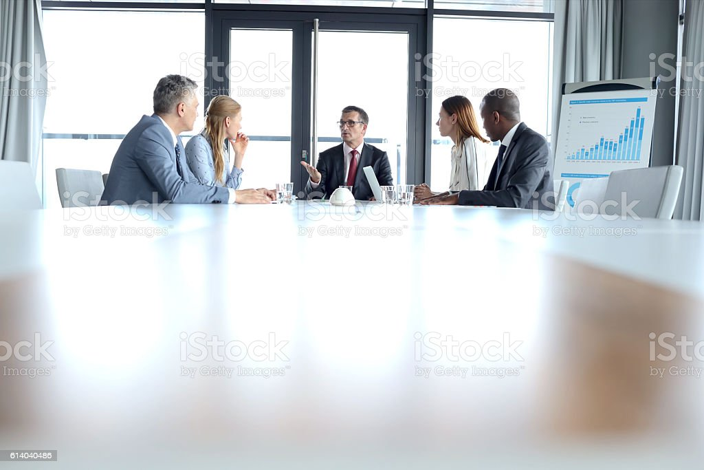 Multi-ethnic business people having discussion at table in board room stock photo