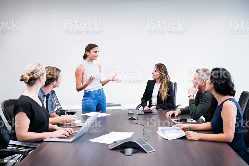 Multiethnic business people in meeting, woman explaining to colleagues stock photo