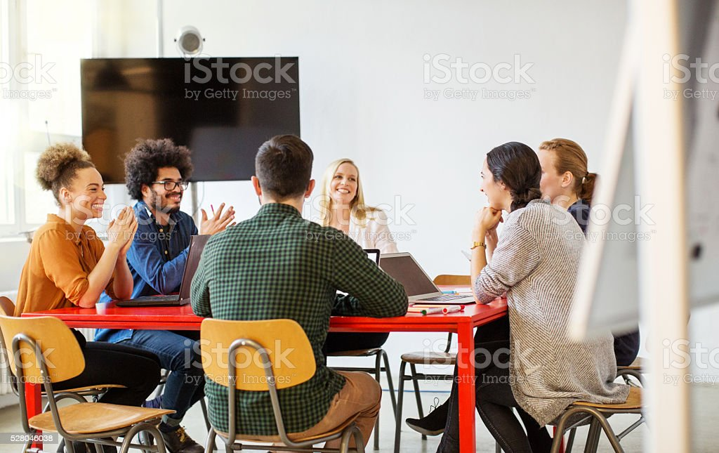 Multi-ethnic business people smiling in meeting stock photo