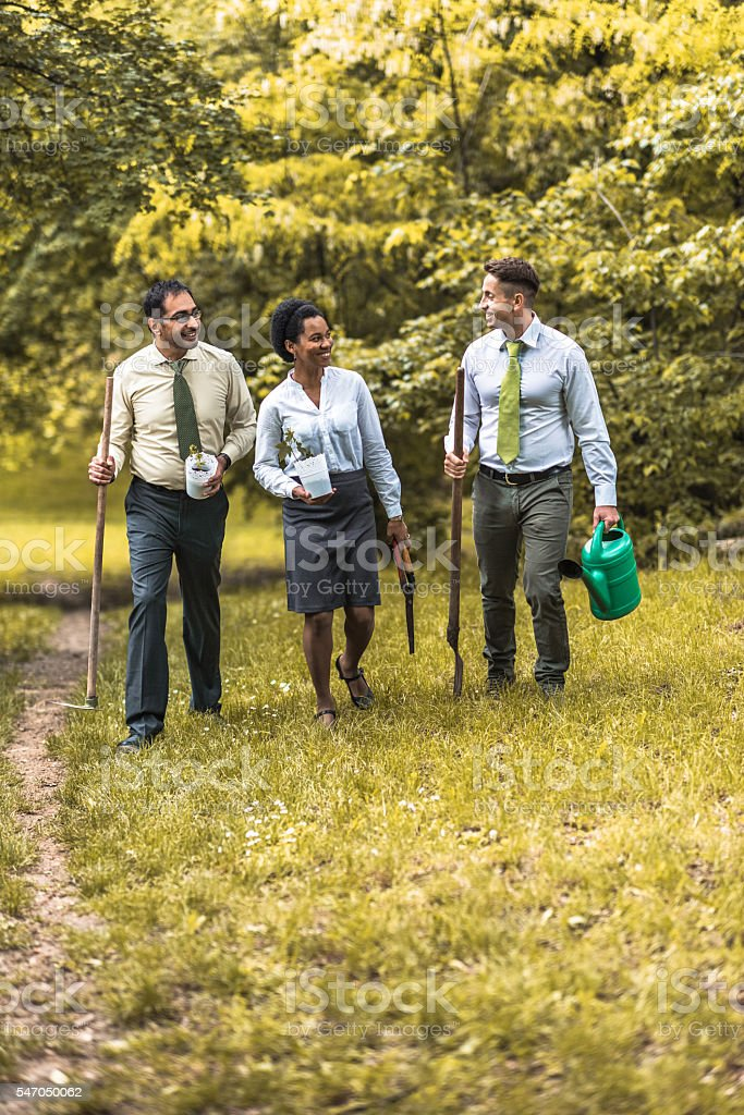 Multi-ethnic business team walking in the park and communicating. stock photo