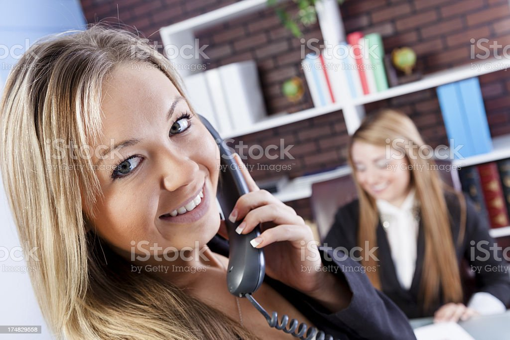 Multi-ethnic business women.  Smiling on the phone, coworker at desk royalty-free stock photo