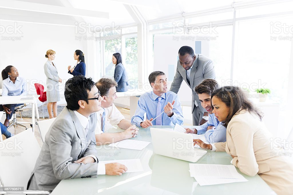 Multiethnic businesspeople meeting around table stock photo