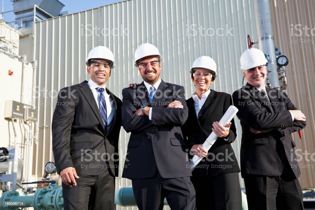 Multi-ethnic businesspeople outside industrial plant royalty-free stock photo