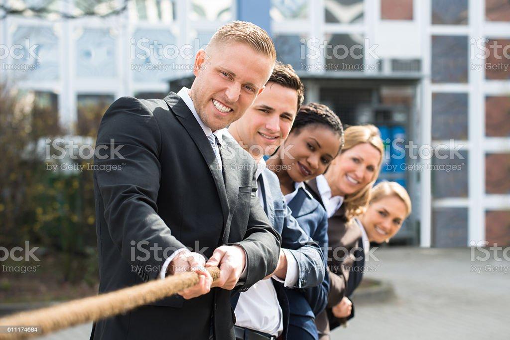 Multiethnic Businesspeople Playing Tug Of War stock photo
