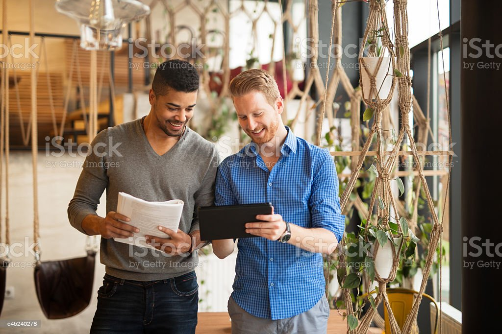 Multi-ethnic casual businessmen having meeting in coffee shop. stock photo