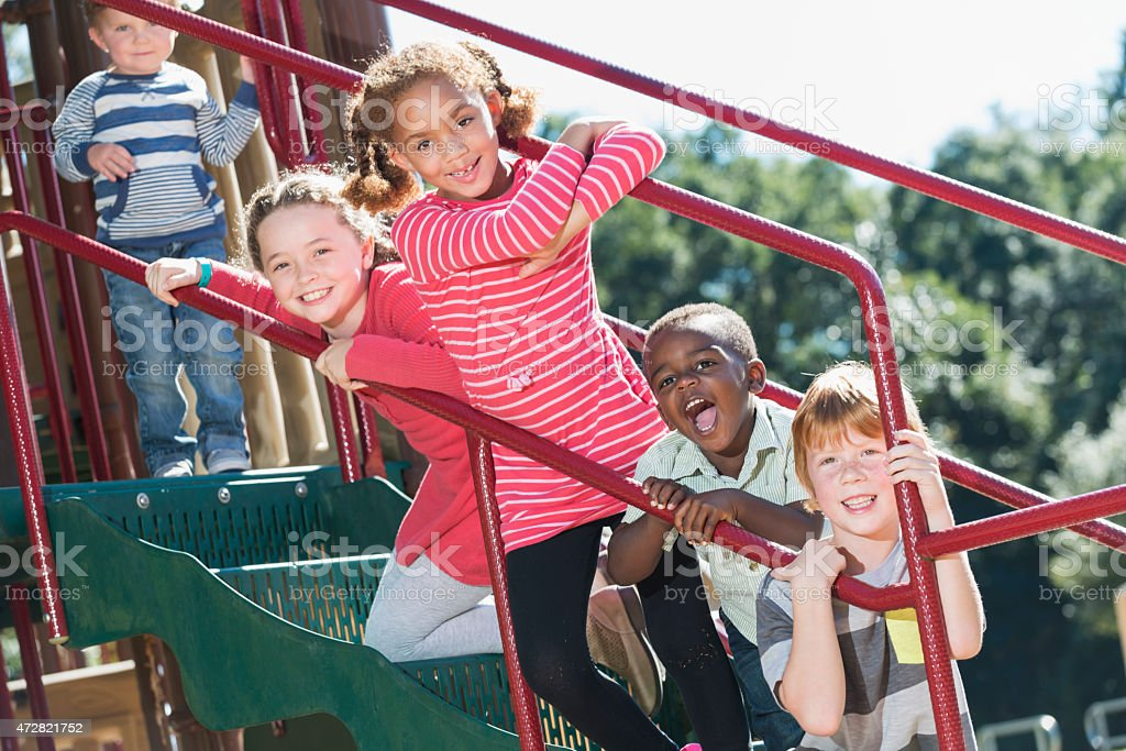Multi-ethnic children having fun at playground stock photo