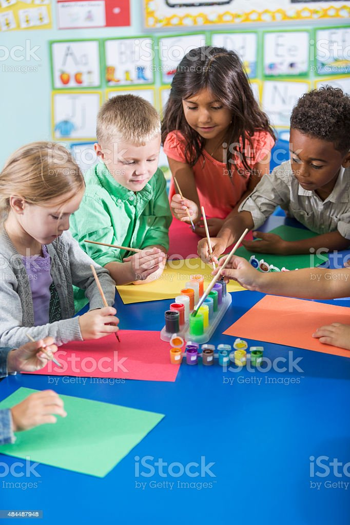 Multi-ethnic children in kindergarten doing art project stock photo