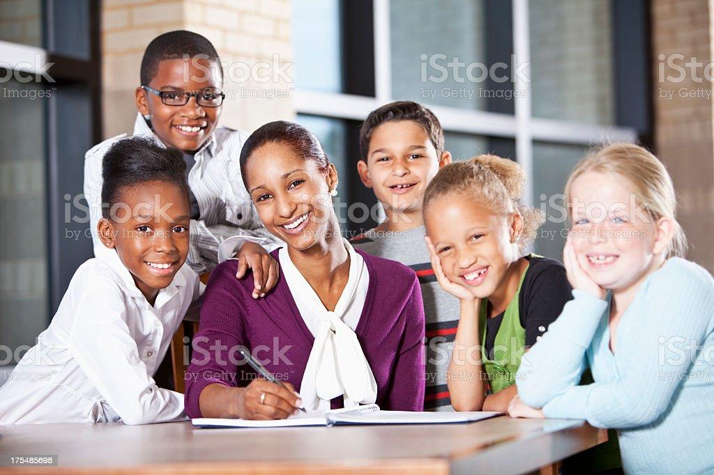 Multi-ethnic children in school with teacher stock photo