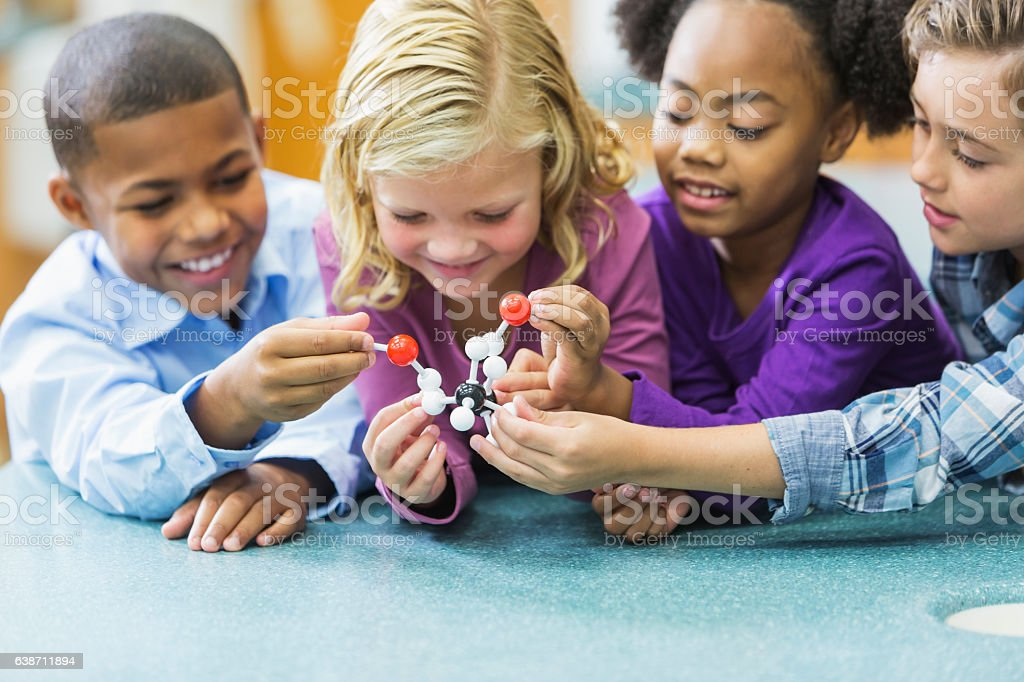 Multi-ethnic children in science class with model stock photo