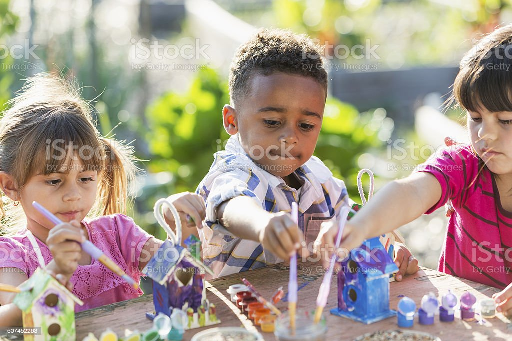 Multi-ethnic children painting bird houses outdoors stock photo