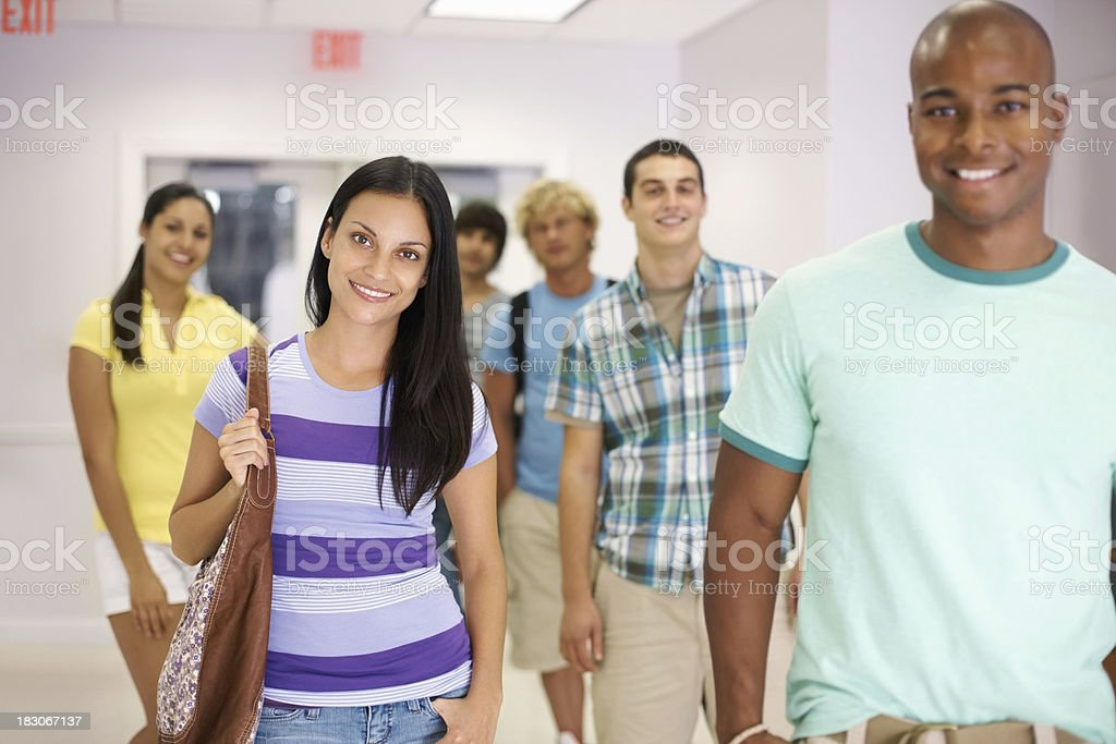 Multi-ethnic college friends standing in university corridor royalty-free stock photo