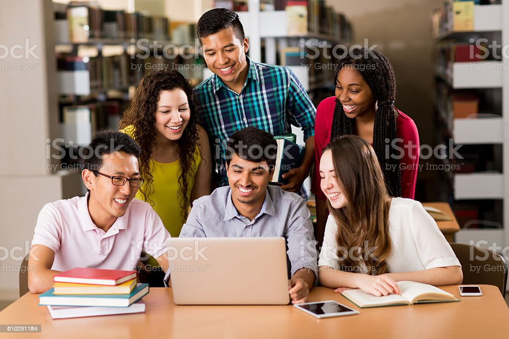 Multi-ethnic college students using laptop in the library stock photo