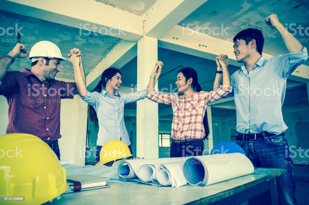 Multiethnic construction engineers waving hands of Corporate Colleagues Teamwork when project success at the building site, Industrial engineering and teamworks Concept stock photo