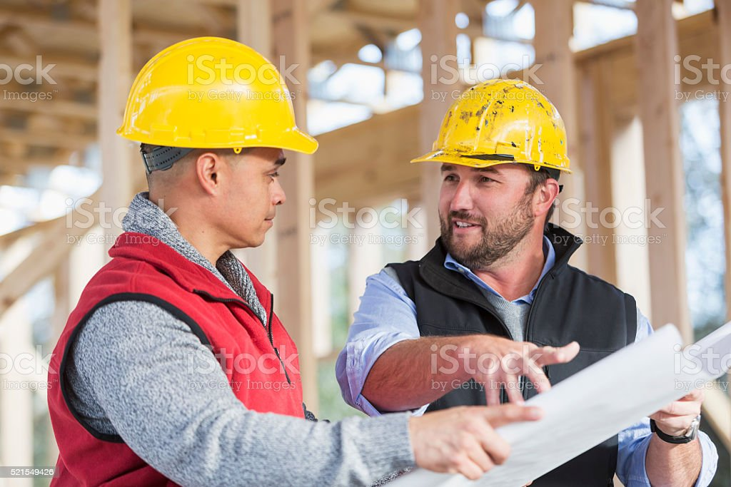Multi-ethnic construction workers with plans, talking stock photo