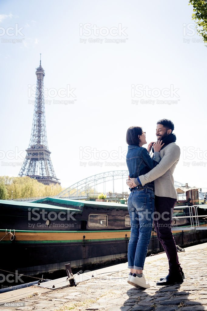 Multi-ethnic couple having fun in Paris near Eiffel Tower stock photo
