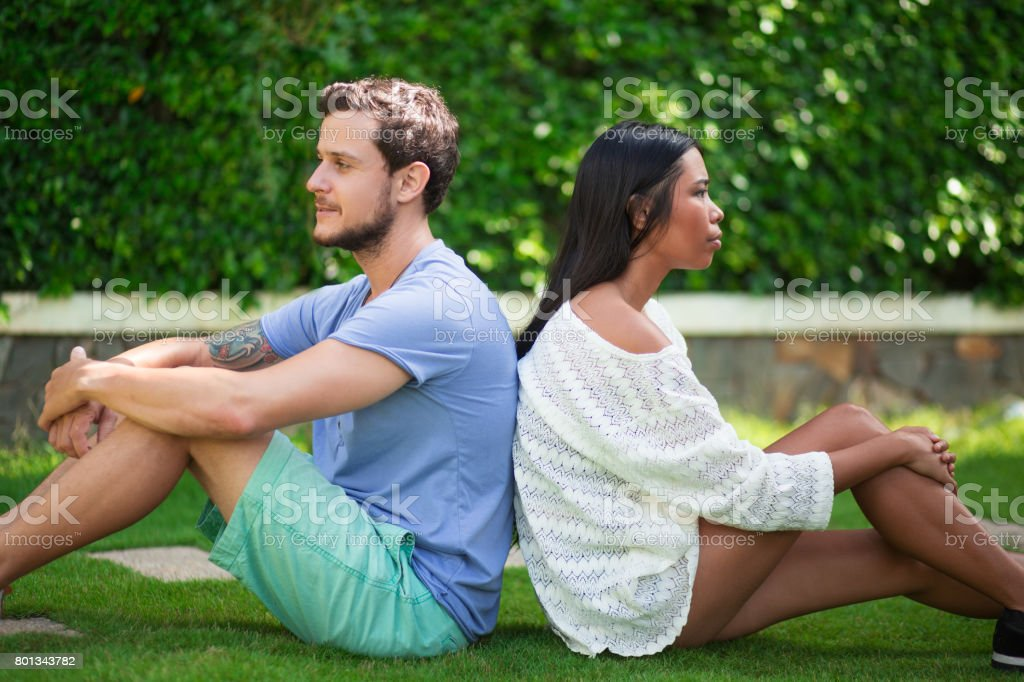 Multi-ethnic Couple Sitting Back to Back on Grass stock photo