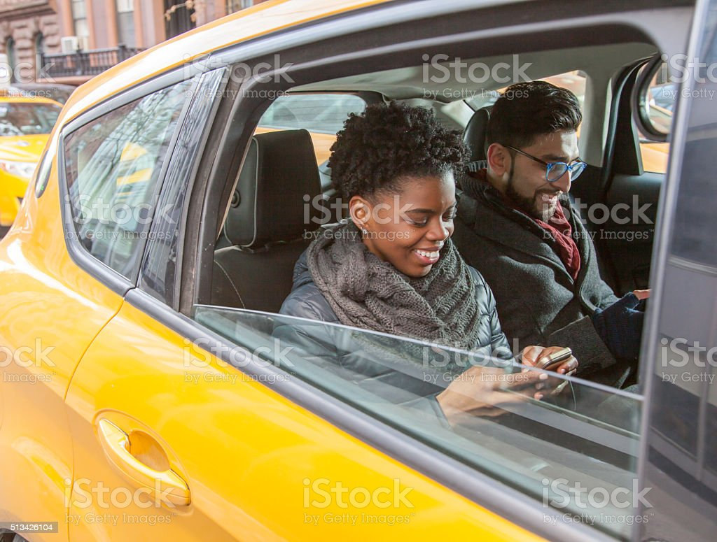 Multi-Ethnic Couple using their Mobile Phones in Taxi Cab stock photo