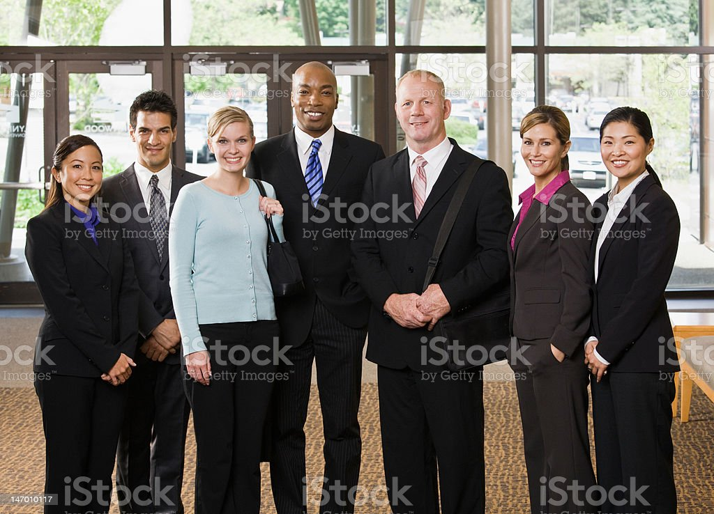 Multi-ethnic co-workers posing in office lobby royalty-free stock photo