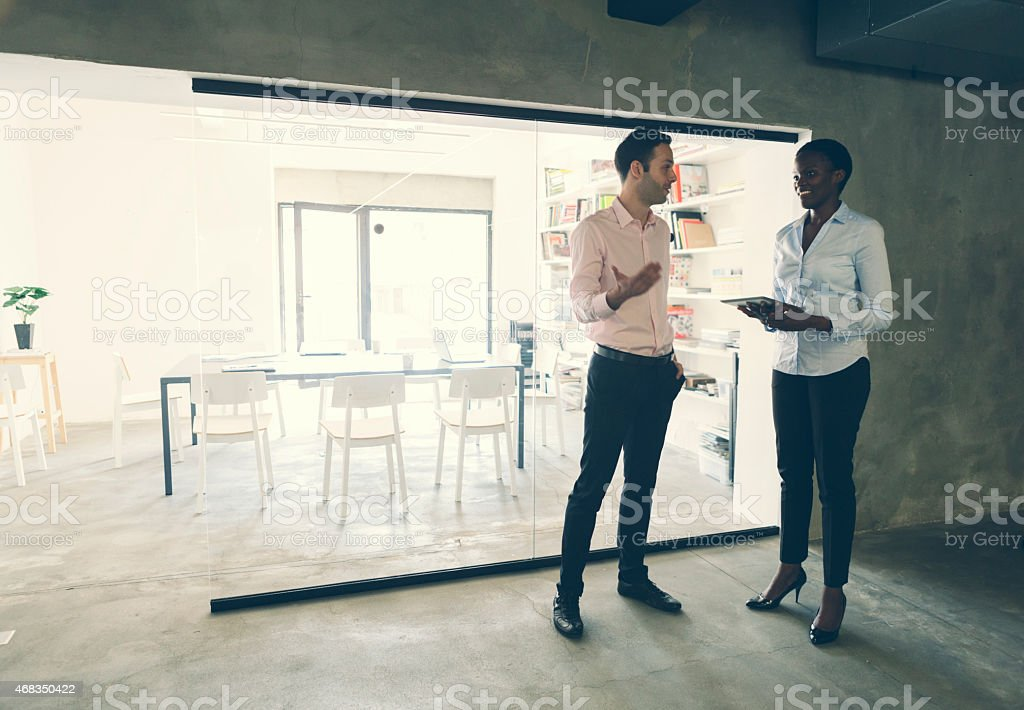 Multi-ethnic Coworkers talking in front of an office. stock photo