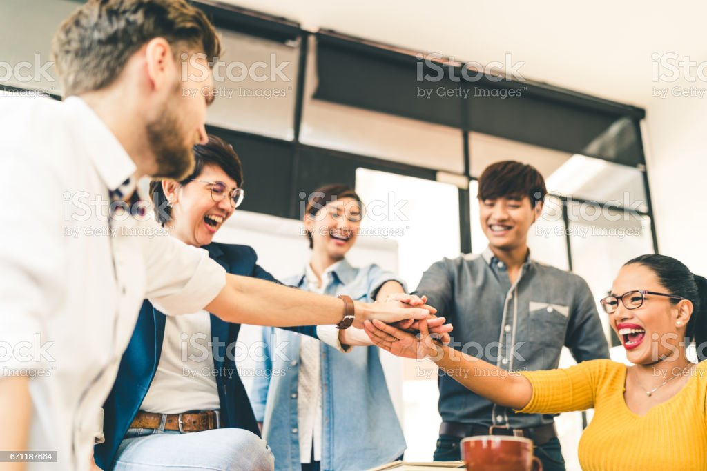 Multiethnic diverse group of happy colleagues join hands together. Creative team, casual business coworker, or college students in project meeting at modern office. Startup or teamwork concept stock photo