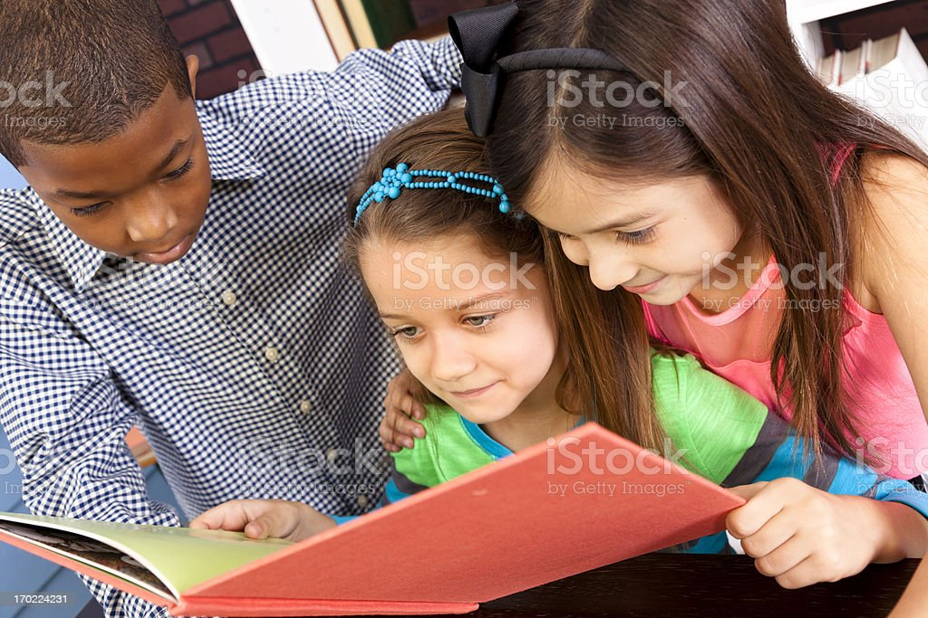 Multi-ethnic Elementary 7-8 year olds looking at book school library royalty-free stock photo