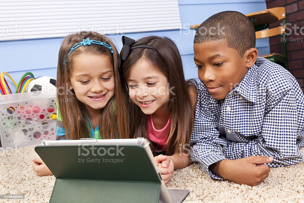 Multi-ethnic Elementary 7-8 year olds looking at digital tablet school. royalty-free stock photo