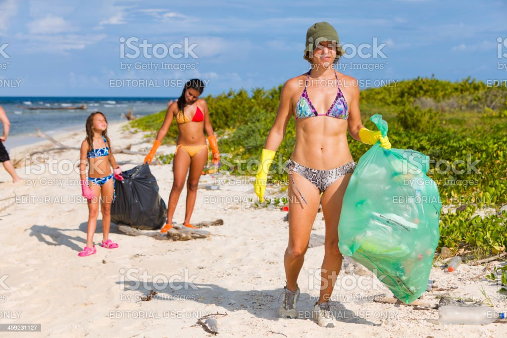 Multi-Ethnic environmental conscious people cleaning tropical beach stock photo