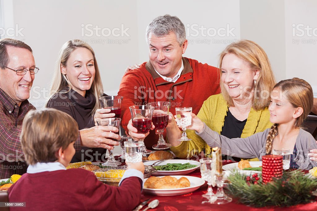 Multi-ethnic family at dinner table, toasting royalty-free stock photo