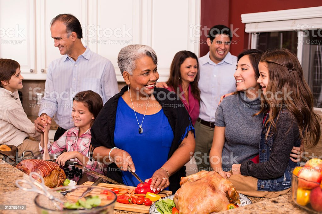 Multi-ethnic family cooks Thanksgiving, Christmas dinner in grandmother's home kitchen. stock photo