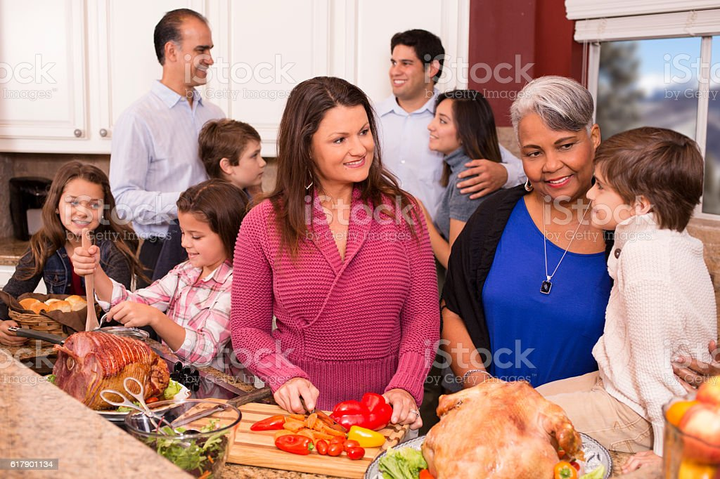 Multi-ethnic family cooks Thanksgiving, Christmas dinner in grandmother's home kitchen. stock photo