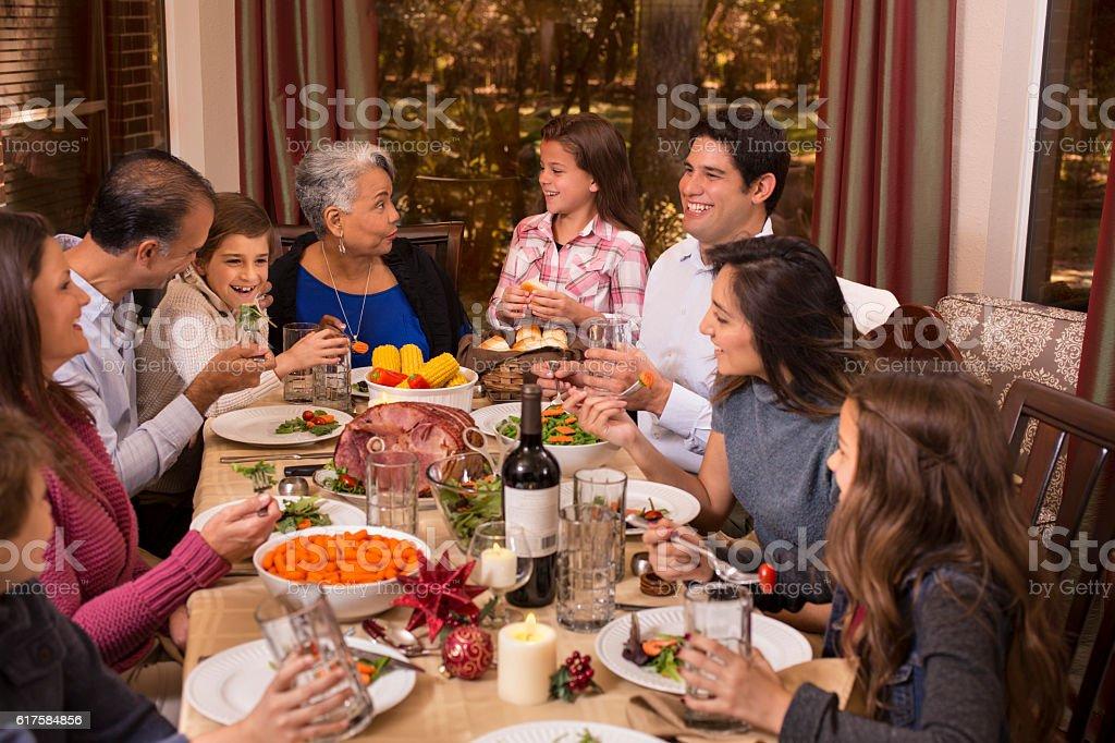Multi-ethnic family enjoying Christmas dinner at grandmother's home. stock photo