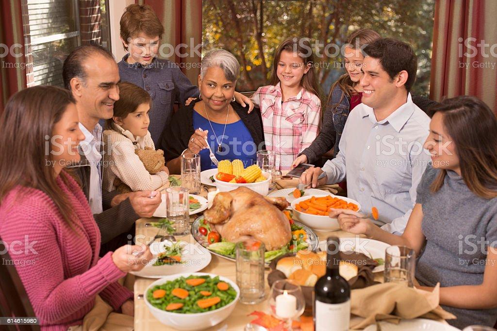 Multi-ethnic family enjoying Thanksgiving dinner at grandmother's home. stock photo