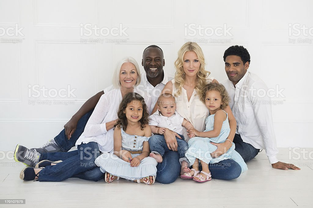 Multi-Ethnic Family Sitting Together Against White Wall royalty-free stock photo